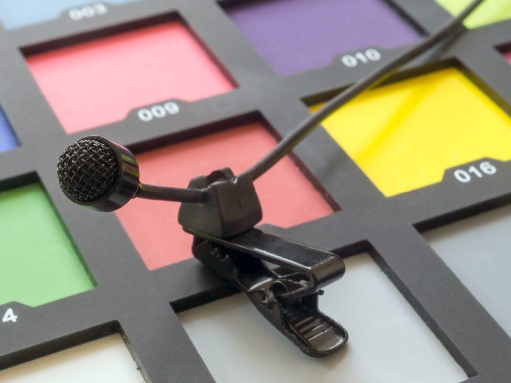 Foto van de geteste JK MIC J-044. Voor de foto van de JK MIC J-044 voor de review, ligt de dasspeldmicrofoon op een color card.