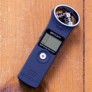 Foto van de Zoom H1 audiorecorder op een planken ondergrond.