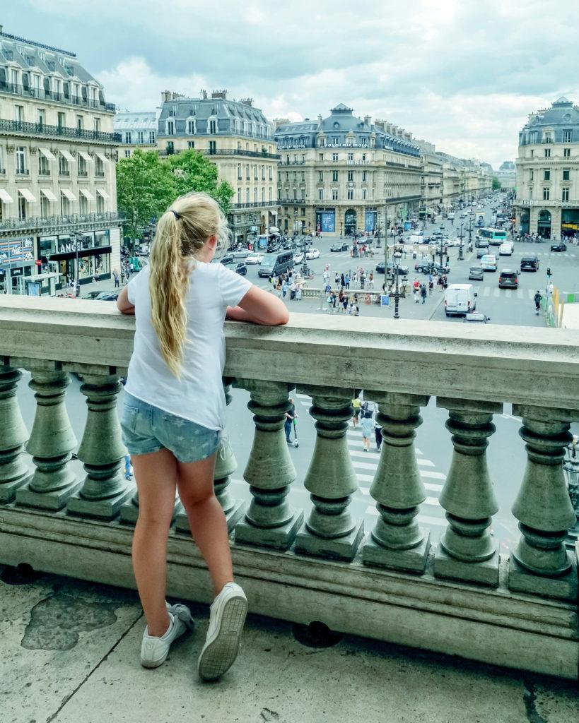 Foto van meisje dat van het balkon van Opéra Garnier uitkijkt over de Place de l'Opéra in Parijs.