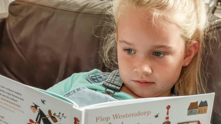 """Foto van meisje dat in het boek """"Fiep in het verkeer"""" leest."""